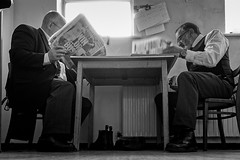 Catching up on the news (aquanout) Tags: people blackandwhite monochrome work table chairs