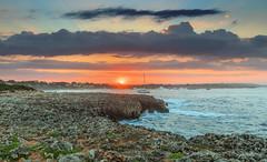 Sunrise Waves (nicklucas2) Tags: menorca sonxoriguer seascape beach boat yacht rock sea sun cloud sunrise lava travel wave