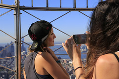 Capturing her friend (erichudson78) Tags: nyc manhattan midtown streetphotography newyorkcity empirestatebuilding canonef24105mmf4lisusm canoneos6d cellphone femme woman cap casquette ciel sky town ville skyscraper gratteciel