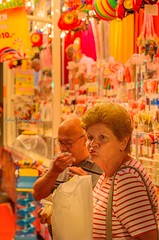 Sweets for my sweet, sugar for my honey (Robica Photography) Tags: robicaphotography streetphotography d3200 people detilburgsekermis 2018 evening funfair fair amusement man woman eating sweets candy shop sugar artificiallight portrait