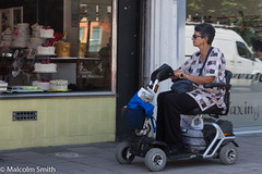 The Cake Distraction (M C Smith) Tags: mobility scooter woman shop cakes window display pavement shopping bags pentax k3ii mesh reflections van white yellow tiles food blue black red gold letters sign sitting newspaper chrome silver green