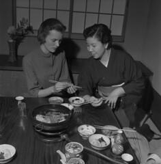 Colleen Watt instructed on how to use chopsticks by a server at a Japanese restaurant, Tokyo, Japan / Colleen Watt se faisant expliquer par une serveuse comment utiliser ses baguettes dans un restaurant japonais, Tokyo (Japon)