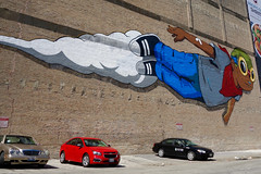 an ephemeral Flyboy (KevinIrvineChi) Tags: hebru brantley hebrubrantley flyboy mural street art streetart south wabash loop chicago illinois brick wall parked cars red blue flying goggles tuskegee airmen bandaid bandage kerchief gray tshirt jeans gym shoes black mercedes parking lot ephemera ephemeral sony dscrx100 outdoors sunny day chevy chevrolet