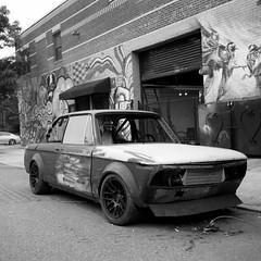 Fixer-Upper (colinpoe) Tags: blackandwhite tmax100 mediumformat 6x6 grafitti garage bushwick car urban rolleiflexautomat rolleiflex bmw2002 nyc newyorkcity rolleiflexautomatk4a kodakfilm bmw bw automobile tlr 120