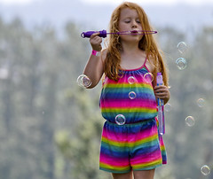 Bubbles and rainbows (albertusmagnus) Tags: candid candidportrait candidstreetportrait streetphotography redhairedyounggirl ginger freckles bubbles blowingbubbles naturallight thejoysofyouth colourful missionfolkmusicfestival nikond5000 nikkor70300mmlens albertusmagnus
