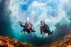 Diving under a cliff (Beth Bennett & Gérard Cachon) Tags: sea ocean diving scuba underwater caribbean bonaire cliff shore waves surf surge swell divers spelunk reef wideangle fisheye nauticam bonaireadventurescuba bas eastcoast tokina 1017
