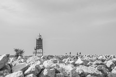 on the rocks (Literal Titles 'R Us) (Clickumentary) Tags: lighthouse breakwater people sky minimal blackandwhite bw black white lake michigan freshwater rip rap trespassing marina boats shoreline rugged