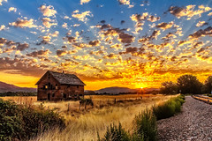 A Vivid Sunrise (http://fineartamerica.com/profiles/robert-bales.ht) Tags: aupload forupload gemcounty haybales idaho land people photo places projects states sunsetorsunrise barn sunrise sunset house farm homestead ranch cattle barnwood fence butte squawbutte mountain idado landscape emmett treasurevalley scenicbiway americaphotography valley idahophotography beautiful sensational spectacular magnificent surreal sublime magical spiritual inspiring canonshooter scenic wow stupendous superb building grass hay trees yellow blue robertbales sky railroad tracks panoramic pano