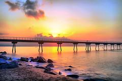 Sunrise behind clouds (Fnikos) Tags: sea water mar mare wave landscape seascape dark light bridge puente pont pier sun sunrise cloud architecture construction rock sky skyline bay outdoor