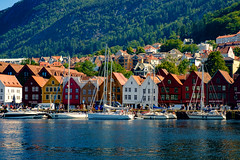 Bryggen on a Summer Day (Bergen, Norway) (briburt) Tags: briburt fujifilm xe1 xf1855 mountains sun water glacial summer light norway norwegian blue glow sky azure panorama landscape dramatic contrast majestic bergen bryggen wharf sail sailboats boats shore maritime houses structure trees unesco world heritage site unescoworldheritagesite tree forest boat city harbor waterfront pier dock hanseatic hansa ocean building mountain