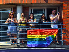 Enjoying the VIew (Owen J Fitzpatrick) Tags: ojf people photography nikon fitzpatrick owen pretty pavement chasing d3100 ireland editorial use only ojfitzpatrick eire dublin republic city tamron candid joe candidphotography candidphoto unposed natural attractive beauty beautiful woman female lady j face hair along photoshoot street 2018 streetphoto pride parade colour colourful apartment balcony flag rainbow railing smile happy happiness sunglasses shades brick view