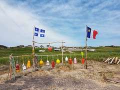 Day 2 - Fishing buoys and flags along the beach at Bassin.  (The campsite is in the background.) (Bobcatnorth) Tags: lesilesdelamadeleine magdalenislands quebec canada summer 2018 cycling velo bicycle bicycling cycletouring bicycletouring touring tourdevelo gulfofstlawrence