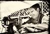 Stitching under the Umbrella (Jean Ka) Tags: approved nepal népal kathmandu kathmandou street rue strase smile lächeln sourire machineàcoudre nähmachine stitchingmachine umbrella regenschirm parapluie schneiderin couturière tailor