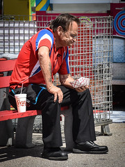 Lunch Break (tim.perdue) Tags: ohio state fair 2018 summer exposition center columbus street candid colorful multicolored midway carnival man person figure old carny worker lunch break eating seated food drink cup coke cocacola red white blue wrinkled weathered tattoo bench hard life