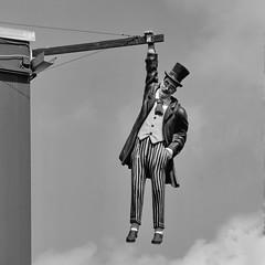 The hanging man in Iaşi, Romania (gerard eder) Tags: world travel reise viajes europa europe romania iaşi iasi blackandwhite blackwhite blancoynegro bw monochrome sculpture escultura skulptur outdoor street streetlife streetart städte stadtlandschaft
