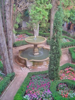 One of the many beautiful fountains within the gardens of the Alhambra, which is a palace and fortress complex located in Granada, Spain. The architecture, the gardens and the backdrop of the Sierra Nevada Mountains in the background make this fortress a