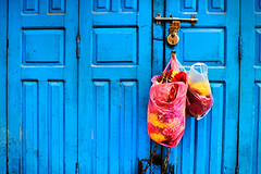 Flowers hanging on a blue door at Shree Pashupatinath Temple, Kathmandu, Nepal (BryonLippincott) Tags: nepal asia asian centralasia pashupatinath kathmandu pashutatinathtemple nepalese nepali outside outdoors day daytime travel destination tourism tourist attraction city urban bright colorful bowl vendor shop stall forsale multicolored traditional market closeup selectivefocus differentialfocus goods selling culture tradition vivid vibrantflowers