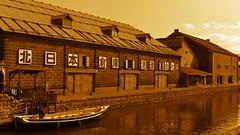 Warehouse along Otaru Canal (Long Sleeper) Tags: street canal otarucanal building architecture warehouse water boat reflections sky sepia monochrome october otaru hokkaido japan dmcgx1