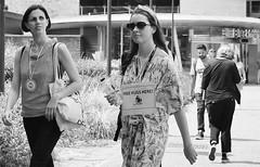 FREE HUGS HERE!.... (markwilkins64) Tags: water sunglasses free hugs women london southbank southwark blackfriars street streetphotography streetscene candid mono monochrome blackandwhite bw blackfriarsstation