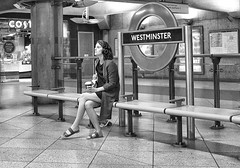 Go West Young Lady (tcees) Tags: westminsterundergroundstn london sw1 londontransport jubileeline districtline circleline urban x100 fujifilm finepix streetphotography street bw mono monochrome blackandwhite woman costacoffee bench roundel light sign floor tiles wall barrier headphones cup coffee map uk