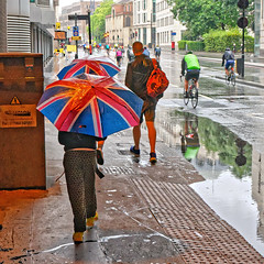 Rainy Day (Geoff Henson) Tags: brolly umbrella flag unionflag unionjack people puddle cyclist bicycle bike rain water pavement road