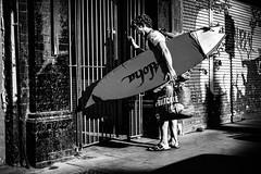 Aloha (Kieron Ellis) Tags: man surfboard bag sandals gate wall pavement graffiti shadow light backpack street candid blackandwhite blackwhite monochrome