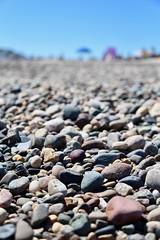 Stone DoF (Read2me) Tags: beach rexhame sand ground umbrella stones pebbles bluesky dof many friendlychallenges thechallengefactory pregamewinner gamesweepwinner challengeyouwinner 15challengeswinner perpetualchallengewinner gamex2 yourock