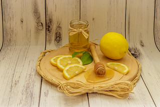 Golden honey in a jar, lemon slices and lemon leaves on a wooden plate on white wooden background