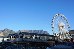 V&A Waterfront, Cape Town, South Africa (mattk1979) Tags: southafrica capetown sun outdoors sky clouds city mountains ocean tablebay water victoriabasin vawaterfront jetty fishing boats ferris wheel above aerial