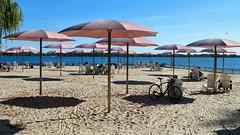 Toronto, Ontario (duaneschermerhorn) Tags: beach sand urban umbrella umbrellas parasol parasols shadows lake water lakeontario sky blue clouds white
