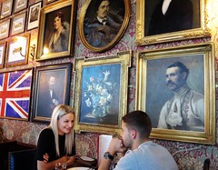 Sharing a cosy moment. (With Nicole) Tags: restaurant uk europe couple paintings candid laughing
