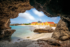 View from a sea cave (Beth Bennett & Gérard Cachon) Tags: washington slagbaai national park bocaslagbaai bonaire netherlandantilles cave longexposure ocean sand beach sky clouds water orange caribbean