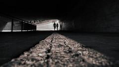 Connected (marionrosengarten) Tags: silhouettes darkness underpass lowpov street light shadow schatten paar pair handinhand walker tunnel schwarzweis bw mono monochrome stone bottom nikon architektur bridge