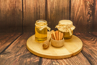Golden honey in a jars and cinnamon sticks on wooden plate on wooden background