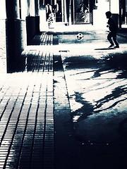 Playing football in the street. (gemaalbornoz) Tags: child simplicity simple minimalist minimalism minimal street blackandwhite bnw