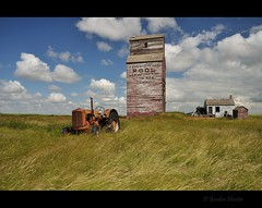 life is short (Gordon Hunter) Tags: prairies grain elevator tractor shed old abandoned decay weathered peeling paint damage grass field clouds sky summer tower building farming agriculture dankin sk saskatchewan rural countryside canada gordon hunter nikon d5000