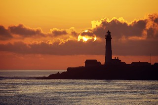 Fiery sun over a lonely lighthouse