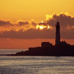 Fiery sun over a lonely lighthouse thumbnail