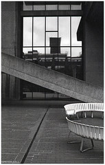 Stairs And Seats (peterphotographic) Tags: img015edwm stairsandseats olympus om2n zuiko ©peterhall barbican barbicancentre london england uk britain jch japanesecamerahunter streetpan400 blackandwhite blackwhitephotos bw monochrome film scanned 35mm architecture modernarchitecture brutal brutalism window stairs seat geometric reflection city cityscape urban