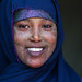 Portrait of a smiling somali woman with qasil on her face and wearing a blue hijab, Woqooyi Galbeed region, Hargeisa, Somaliland