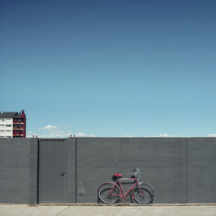The red bike doesn't exist (josemanuelerre) Tags: streetart minimal bike red city urban grey wall building architecture blue sky clouds white detail paint spray trompeloeil landscape cityscape horizon whimsical summer spring clear day construction fantasy front facade door brick town color house empty