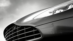 Suggestive (Mr. Pebb) Tags: desaturated blackwhite blackandwhite bw close closeup vent vents grill portion part brit british supercar grandtourer gtcar gt car twoseater 2door 2seater v12engined v12 v12powered britishv12 rwd rearwheeldrive frontengined fr curve curves sky cloud clouds astonmartin db11 granturismosport granturismo pd polyphonydigital sonyinteractiveentertainment sony stock stockshot ps4 playstation4 playstation playstation4pro 4k photomode racegame racinggame