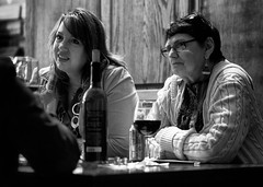 Empathy (Anne Worner) Tags: anneworner bw beer blackandwhite bottle candid caring conversation discussion glass glasses hair indoors intense olympus people silverefex street streetphotography wine winebar winebottle woman compassion jacket earrings table sitting