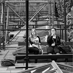 Upon the roof (John Riper - AWAY FOR AWHILE) Tags: johnriper street photography straatfotografie rotterdam square bw black white zwartwit mono monochrome netherlands candid john riper canon 6d 24105 l groot handelsgebouw groothandelsgebouw trap detrap rotterdamviertdestad wederopbouw reconstruction cultural event women ladies eating apple relaxing scaffold wokkels snack chips lays smartphone phone backpack bag girls friends