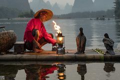 Gas lamp 1 (lc99photography) Tags: fisherman cormorantfisherman cormorantfishing cormorant birds raft bambooraft landscape guilin guangxi lijiang liriver river reflections light gaslamp lamp fire flame face portrait china people red oldman hat mountains karst karstformation bestportraitsaoi