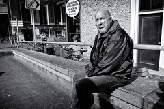 Hair Extension? Let Me Think! (Alfred Grupstra) Tags: men people blackandwhite oneperson outdoors males sitting urbanscene street onemanonly citylife adult city casualclothing onlymen lifestyles portrait realpeople loneliness