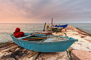 Fishing boats on artificial cliff at sunset.