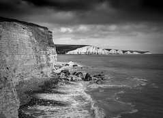 The Seven Sisters (Lloyd Austin) Tags: nikon d7200 sigma1750mm monochrome mono bw blackwhite bnw seaford hills landscape land view vista atmospheric dramatic overcast stormy moody dark cloudscape clouds sky black white stones pebbles rocks sand beach tide waves seascape coastline coastal coast water sea ocean englishchannel sisters seven cliffs chalk england sussex cuckmerehaven hopegap sevensisters