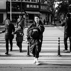 Do not wake him up (Go-tea 郭天) Tags: hangzhoushi zhejiangsheng chine cn linan hangzhou kid child boy woman young mother mama zebra cross crossing pedestrian family carry carring carried harms sleep sleeping tired coat sun sunny shadow care relationship street urban city outside outdoor people candid bw bnw black white blackwhite blackandwhite monochrome naturallight natural light asia asian china chinese canon eos 100d 24mm prime walk walking movement lady