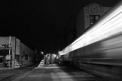 riding the noir line (KevinIrvineChi) Tags: ctabrownline chicago chicagotransitauthority rail heavy train railroad crossing railroadcrossing railroadtracks night noir black blackwhite blackandwhite blanc blanca white bnw bw monochrome gate apartmentbuildings bricks outdoors outside albanypark moving fast lights blur blurry blurred motion rest sony dscrx100 downtown street road pavement transport transit public